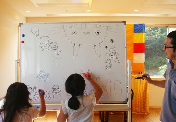 先生が脳トレのために上下を逆に描いています。子供たちは大はしゃぎで周りで描きまくっています。