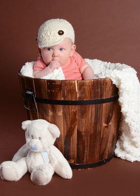 Baby im Holzeimer im Fotostudio