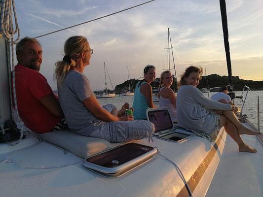 Mit einem Drink auf dem Vorschiff den Sonnenuntergang getrachten