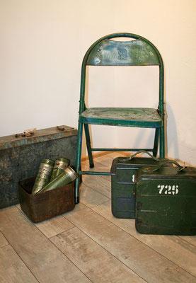 alte Militärbehälter dunkelgrün und Recycling-Eisenstuhl
