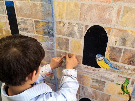 Direkt an der Wand kleben wir auch noch Tiere auf. Dafür suchen wir zusammen die richtigen Plätze aus.