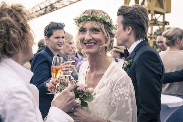 Braut lächelnd, Brautstrauß, Blumenkranz, Terrasse, Location: Fleet 3, Finkenwerder, Hamburg, minalux, wedding photography, Hochzeitsreportage, Mina Esfandiari