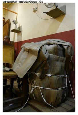Damit die Tabakblätter auf dem Weg in die Fabrik geschützt sind, werden sie erst in Blätter der Königspalme eingewickelt und dann in die Säcke gesteckt.