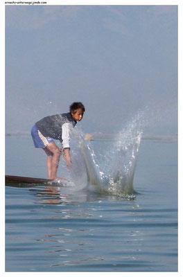 Sie schlagen mit dem Ruder auf das Wasser, um die Fische in den unter dem Boot hängenden Korb zu treiben.