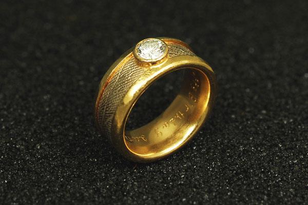 Gelbgoldring mit umlaufendem, in Weißgold gegossenem Handabdruck und rund gefaßtem Brillant