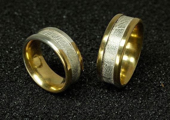 Um den ganzen Ring laufender Handabdruck in Weißgold, umfaßt von Gelbgold