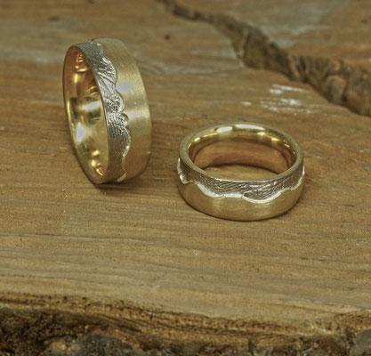 Gelbgoldring mit um den ganzen Ring laufendem Handabdruck in Weißgold, umfaßt von Gelbgold