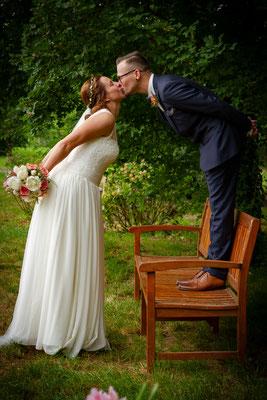 Brautpaar küsst sich auf einer Holzbank