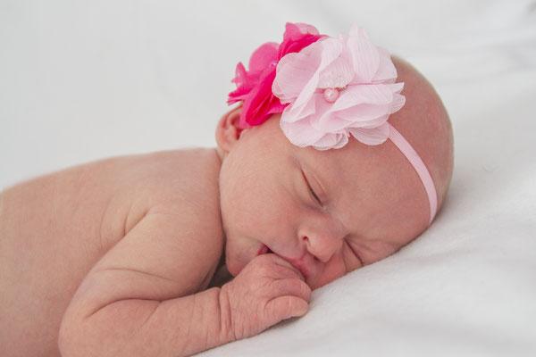 Meine Tochter mit wenigen Tagen mit Blumenhaarband beim Babyshooting