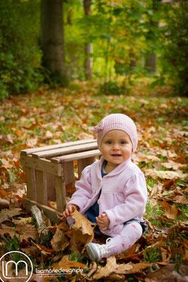 Im Laub sitzen und mit den Blättern spielen macht Spaß.