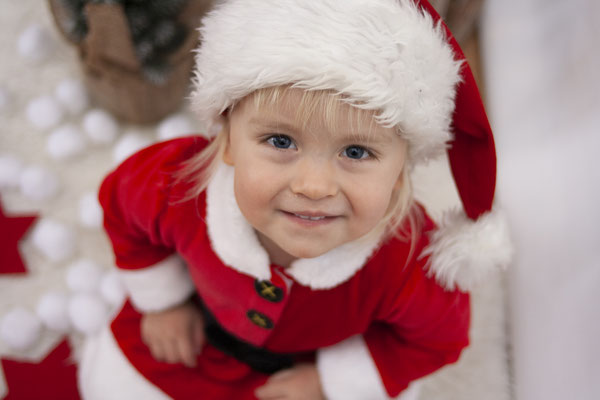 Weihnachtsfotos: Ein kleines Mädchen im Weihnachtsoutfit lacht in die Kamera