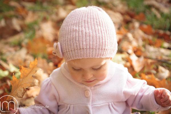 Verträumt schaut sich das kleine Mädchen die bunten Blätter an.