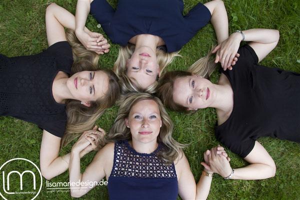 Freundinnenshooting in Leipzig: Vier Freundinnen liegen auf der Wiese und halten die Hände