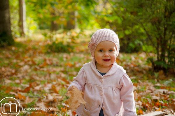 Mit bunten Herbstblättern spielen ist sehr lustig.