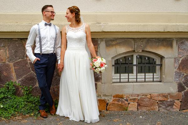 Ganz lässig steht das Brautpaar an einer Hauswand