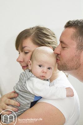 Beim Babyshooting küsste Papa seinen Sohn zärtlich auf den Kopf