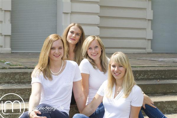 Vier Freundinnen sitzen gut gelaunt auf einer Treppe