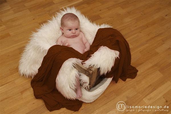 Babyshooting zu Hause als Homeshooting mit einem Korb und warmer Decke