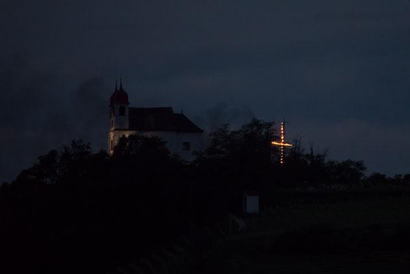 Herz-Jesu 2016: Die Gleifkirche mit einem Flammenkreuz im Hintergrund