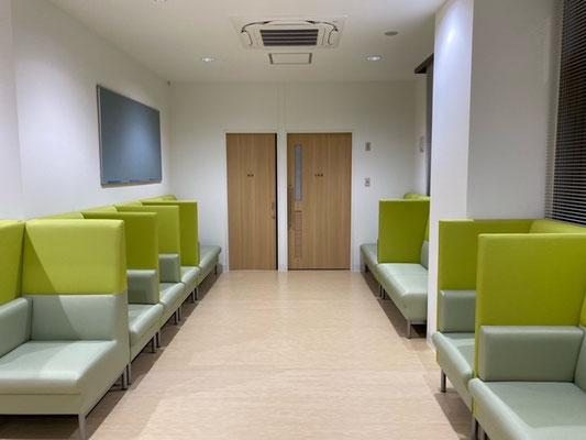 正面から見ると両側にパーテーションのあるソファーが並び、ソファーの緑と床や建具の木目の色合いが合って、とても綺麗です。