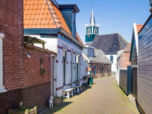 Straatje in het dorp Oudeschild met aan het einde de oude 17e eeuwse Zeemanskerk.