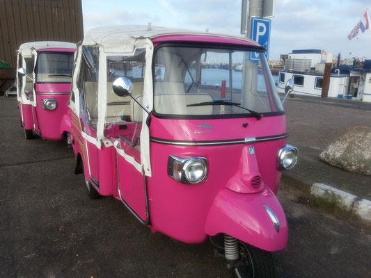 """<img src=""""image.png"""" alt=""""Twee roze Tuk Tuks bij de haven van Oudeschild op Texel"""">"""