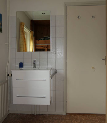 """Slaapkamer met wastafel en spiegel van vakantiehuis """"Groenoord"""" op bungalowpark """"De Parel"""", Texel."""