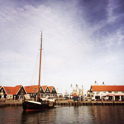 De haven van Oudeschild met wegvarend zeilschip.