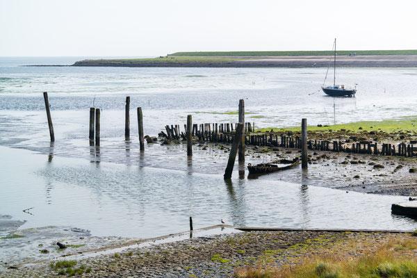 Het haventje van Sil Boon met op de achtergrond een zeilbootje op het drooggevallen Wad.