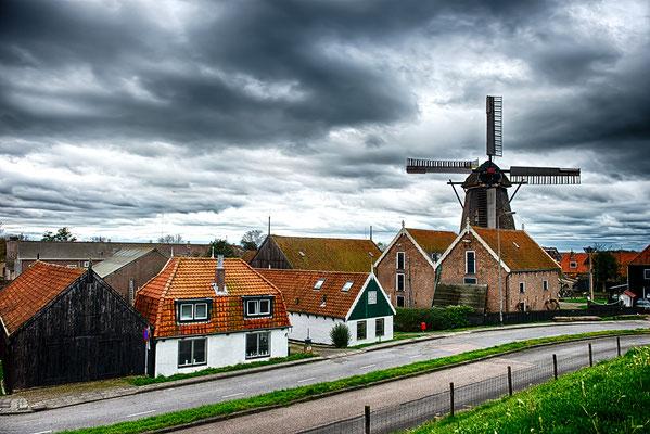 """Het dorp Oudeschild vanaf de dijk gezien met op de achtergrond de korenmolen """"De Traanroeier die in 1902 vanuit Zaandam naar Texel verhuisd is."""