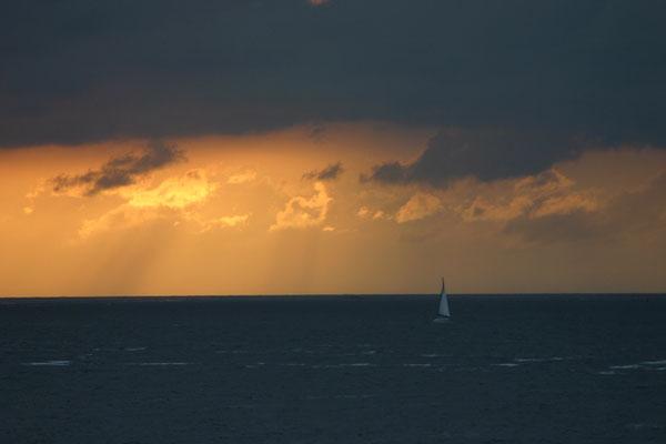 Zeilboot op zee bij zonsondergang.