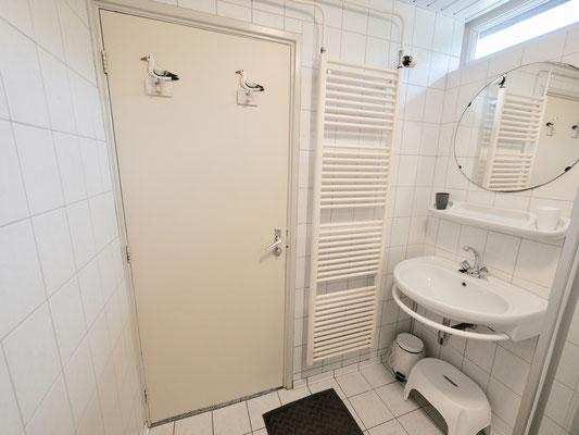 """Badkamer van vakantiehuis """"Groenoord"""" met wastafel en design radiator op bungalowpark """"De Parel"""", Texel."""