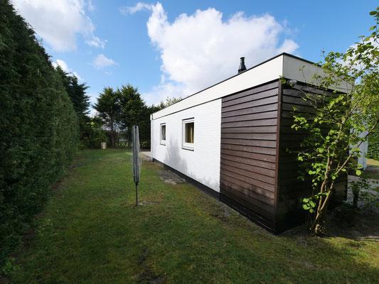 """Zijkant van vakantiehuis """"Groenoord"""" met droogmolen op bungalowpark """"De Parel"""", Texel."""