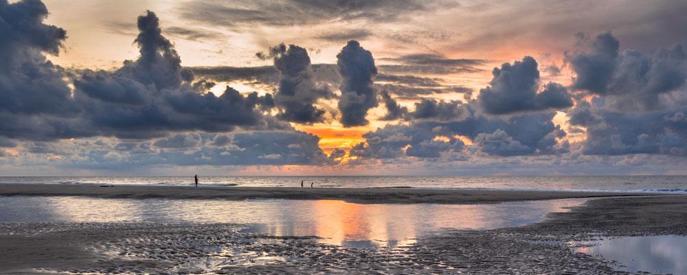 Strandgasten op een zandbank bij zonsondergang.
