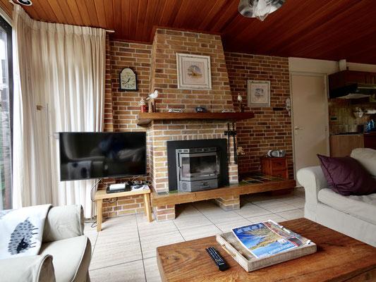 """Interieur van vakantiehuis """"Groenoord"""" met openhaard en flatscreen 4K TV op bungalowpark """"De Parel"""", Texel."""
