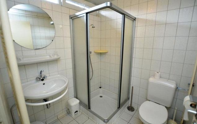 """Badkamer van vakantiehuis """"Groenoord"""" met douchecabine en toilet op bungalowpark """"De Parel"""", Texel."""