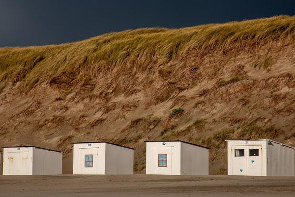 Strandhuisjes met hoge duinen op de achtergrond.