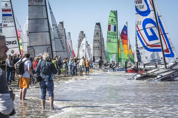"""<img src=""""image.png"""" alt=""""Catamarans op het strand van Texel bij Paal 17,  klaar voor Ronde om Texel"""">"""