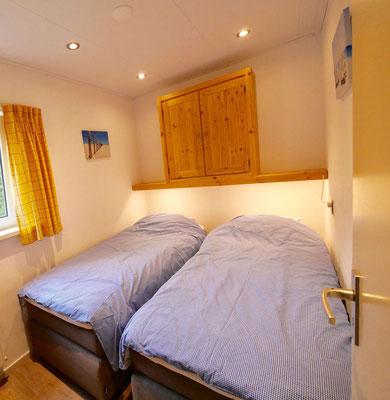 """Slaapkamer met twee éénpersoons boxspring bedden van vakantiehuis """"Groenoord"""" op bungalowpark """"De Parel"""", Texel."""