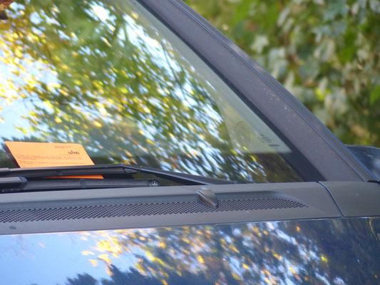 orangefarbener Zettel klemmt an Scheibenwischern weist auf zuküünftiges Parkverbot hin