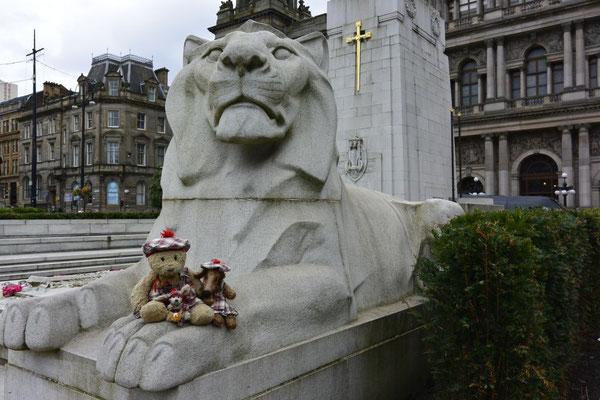 Kasimir, Cäsar und Fredi auf einem der Löwen vor dem Rathaus Glasgows, Schottland