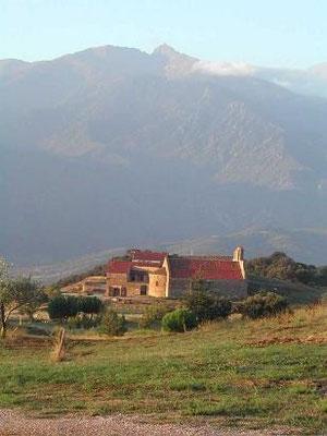 Le prieuré vu de loin, le Canigou derrière