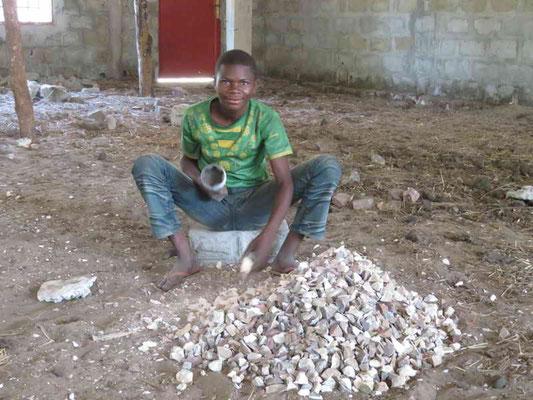 Steine werden von Hand zu Kieselsteinen verarbeitet