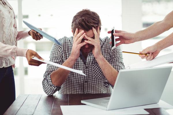 Mann ist verzweifelt, weil er dem Stress und den vielen Aufgaben nicht mehr gewachsen ist. Mentaler Stress, Stress auf der Arbeit, Telefonate, Unterschriften alles prasselt auf ihn ein