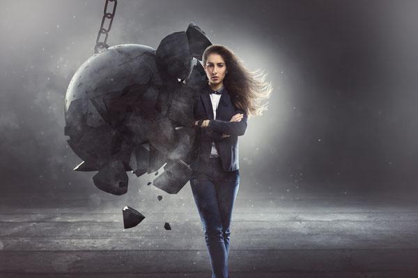 Eine Frau wird von einer Abrisskugel getroffen, jedoch zerbricht diese und nicht die Frau. Dieses ist eine Verbildlichung bzw. Visulisierung von Resilienz