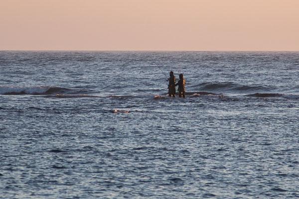 Zwei Angler stehen im Meer
