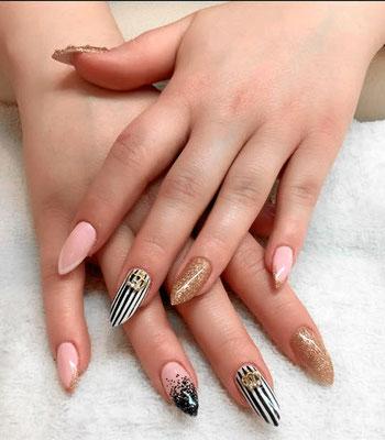 Nude, gold und schwarz-weiß variierende spitze Nägel