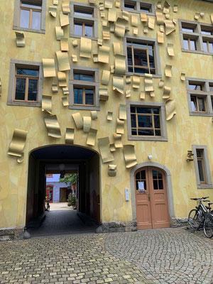 auf der sonnengelben Wand sind goldene Alu-Bleche montiert, die wie hingeweht die Wand verzieren