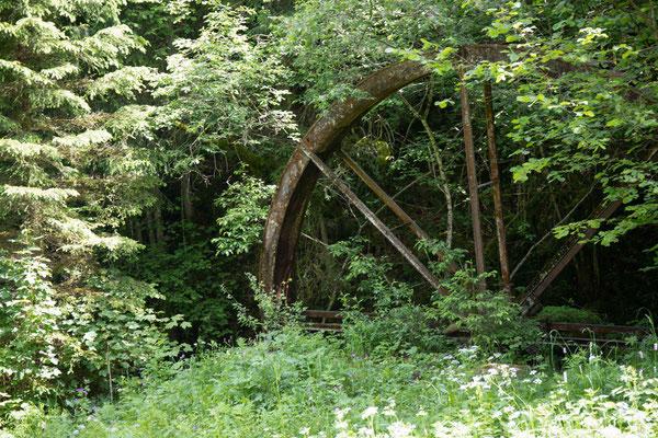Von der Mühle ist nur noch das verrostete Mühlenrad vorhanden