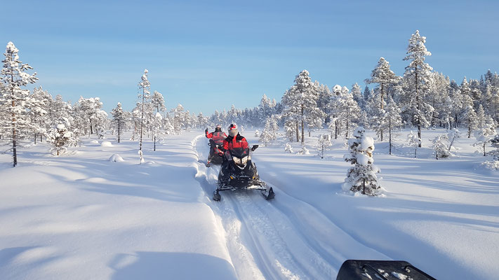 Schöne Tour mit den Schneemobilen bei blauem Himmel